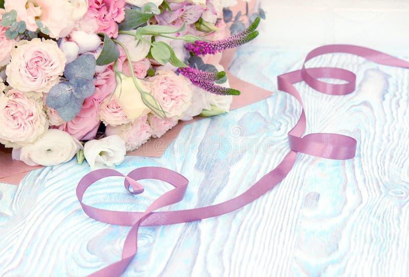 Giorno del `s del biglietto di S Valentine Gift Nastro del raso nella forma del cuore ed in mazzo dei fiori su fondo di legno blu immagine stock
