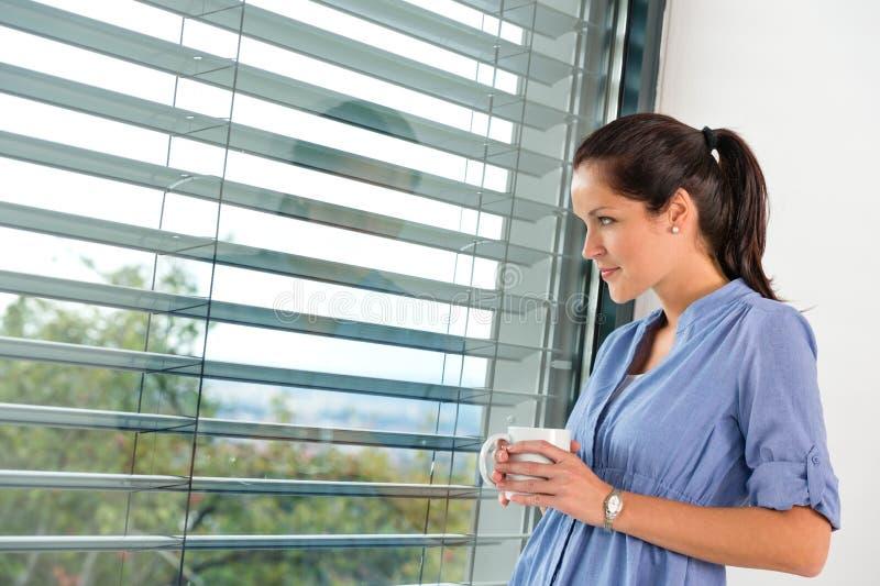 Giorno della giovane donna che sogna guardando i ciechi di finestra immagine stock