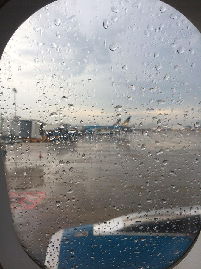 Giorno della pioggia dalla finestra piana fotografia stock libera da diritti