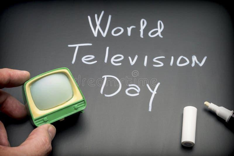 Giorno della televisione del mondo scritto sulla lavagna accanto alla TV miniatura fotografie stock