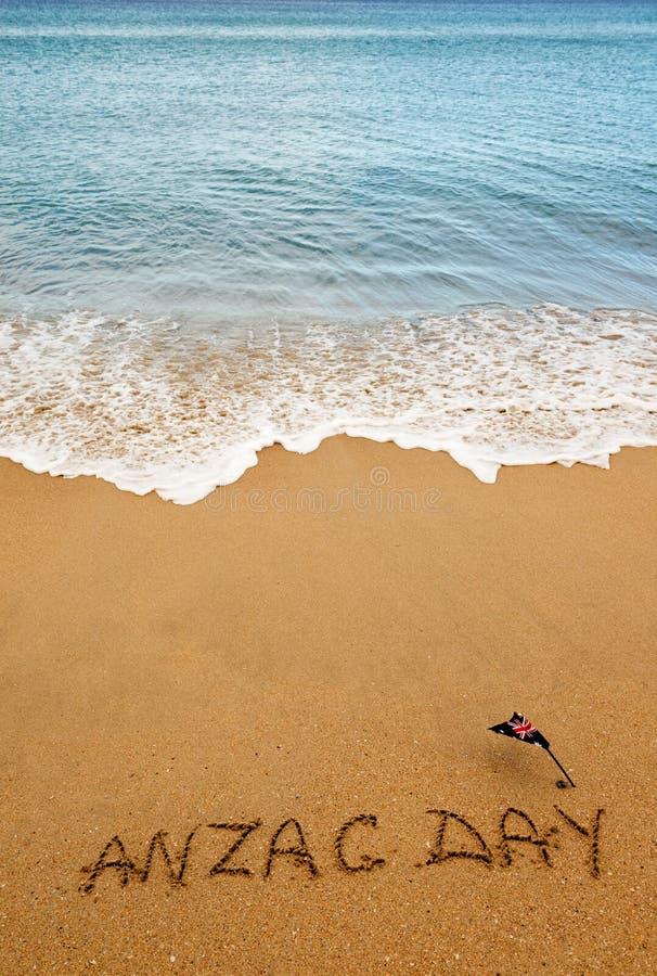 Giorno di Anzac di parole e bandiera australiana sulla sabbia della spiaggia lest fotografia stock libera da diritti