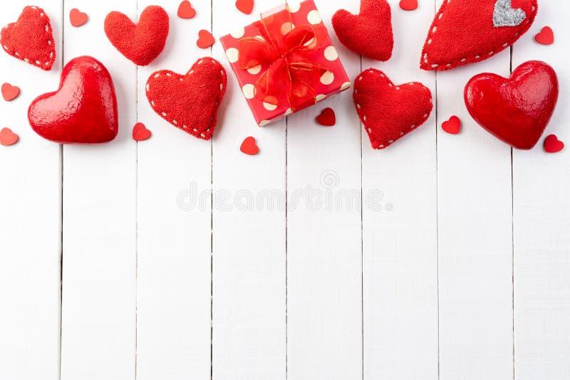 Giorno di biglietti di S cuori rossi fatti a mano con il contenitore di regalo rosso fotografie stock