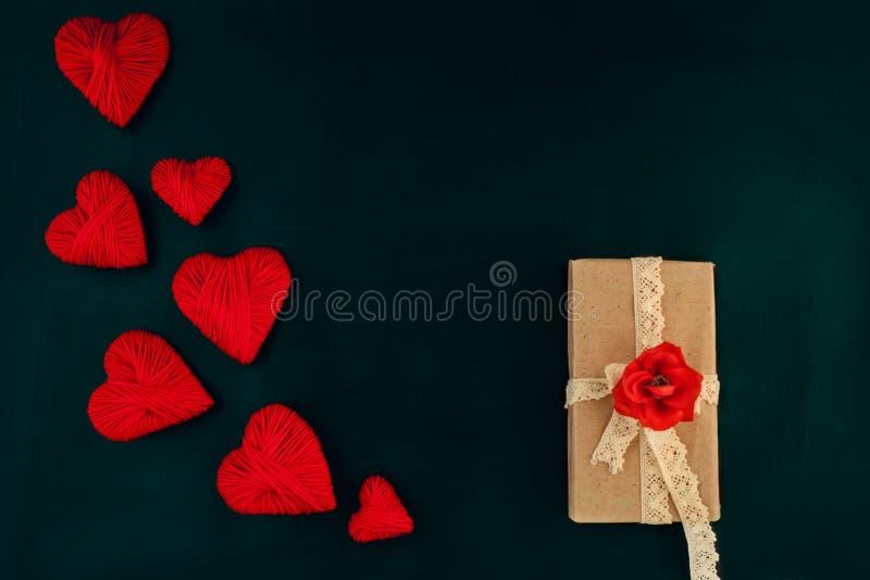 Giorno di biglietti di S. Valentino, cuori rossi su un fondo scuro con un regalo, spazio per testo fotografie stock libere da diritti