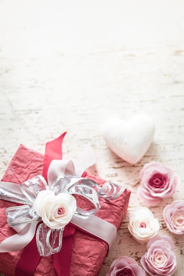Giorno di biglietti di S. Valentino e concetto di festa della mamma, contenitore di regalo rosso con l'arco e rose su fondo di le fotografia stock libera da diritti