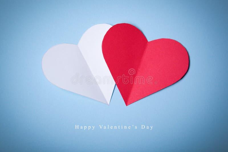 Giorno di biglietti di S. Valentino felice, cuori rossi e bianchi da carta su fondo blu Buona festa immagine stock