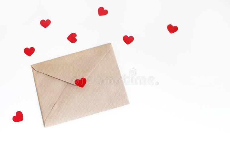 Giorno di biglietti di S. Valentino o scena del modello di nozze con la busta, coriandoli di carta rossi dei cuori isolati su fon fotografia stock
