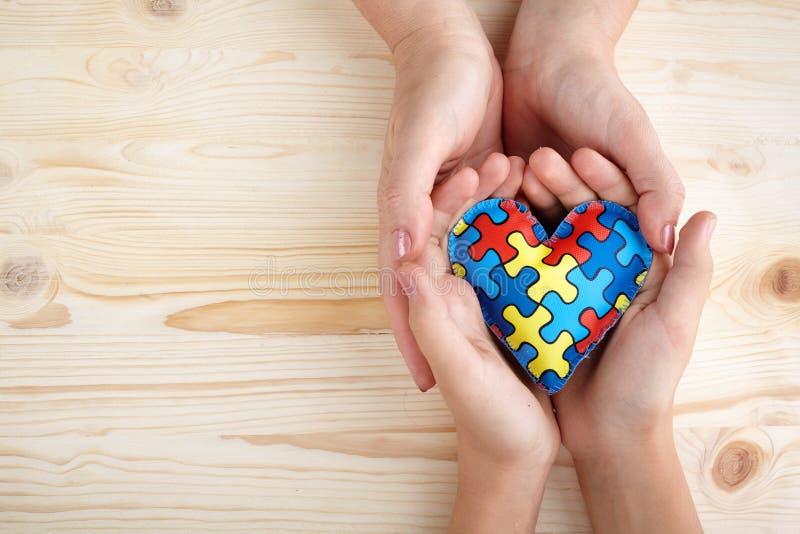 Giorno di consapevolezza di autismo del mondo, puzzle o modello del puzzle su cuore con le mani autistiche delle donne e del bamb immagini stock libere da diritti