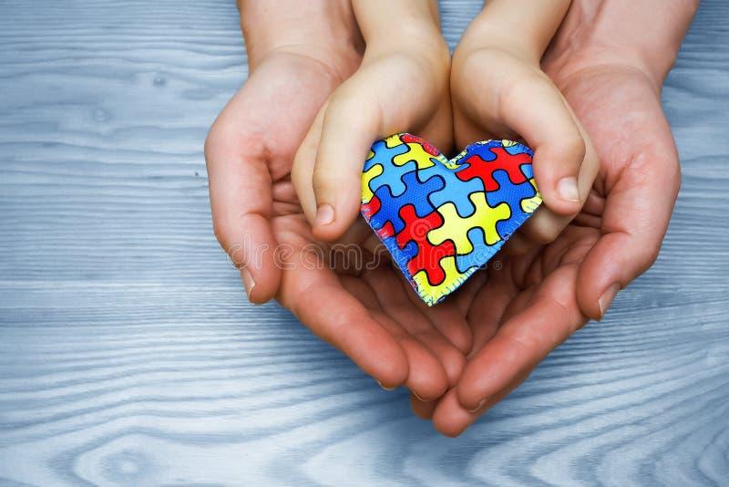 Giorno di consapevolezza di autismo del mondo, puzzle o modello del puzzle su cuore con le mani autistiche del padre e del bambin immagine stock