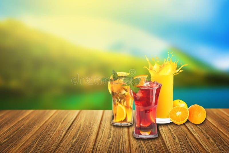 Giorno di estate piacevole! Succo d'arancia di rinfresco e due cocktail di frutta sulla superficie di legno fotografia stock libera da diritti
