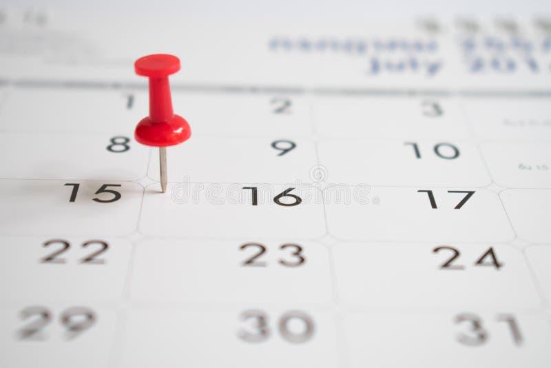 Giorno di evento con un perno rosso sul calendario Fondo immagini stock libere da diritti