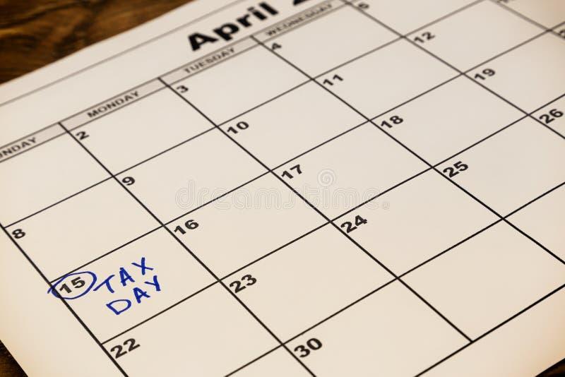 Giorno di imposta di aprile scritto ed appuntato in un calendario, fine su modificato immagini stock