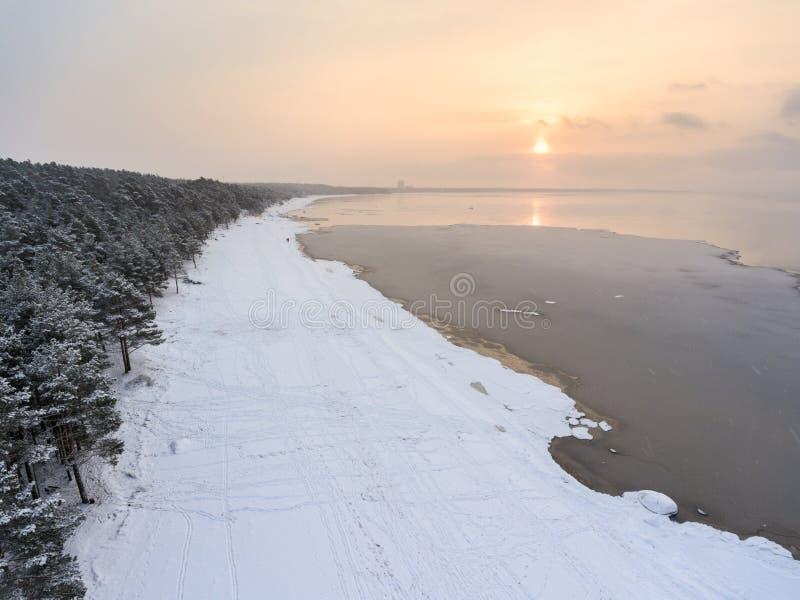 Giorno di inverno con il sole basso e la spiaggia sabbiosa del mare del forte gelo sotto neve con ghiaccio di acqua Siluetta dell fotografia stock libera da diritti