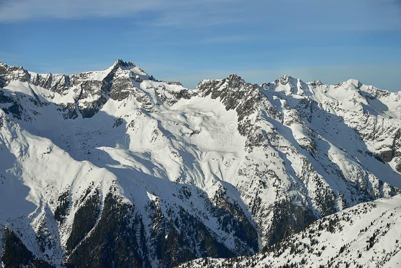 Giorno di inverno soleggiato nelle alpi del Tirolo: pendii e cielo blu di montagna innevati immagini stock