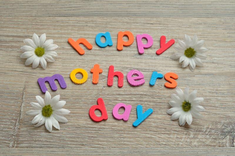 Giorno di madri felice nelle lettere variopinte con le margherite bianche fotografia stock