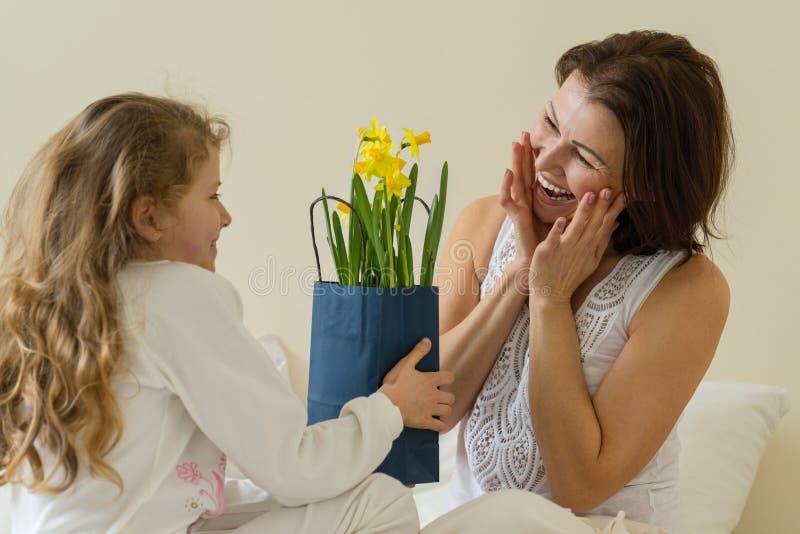 Giorno di madri Una madre felice ha ricevuto il mazzo ed il regalo dalla sua piccola figlia di mattina a letto fotografie stock libere da diritti