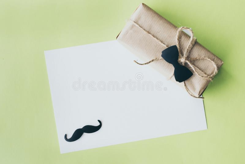 Giorno di padri Pacchetto del regalo avvolto con carta e la corda con una cravatta a farfalla decorativa su fondo verde Copyspace fotografia stock