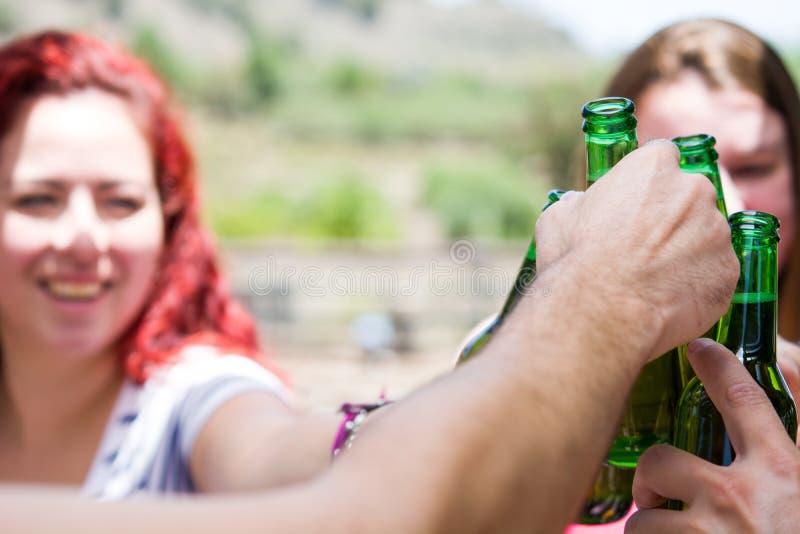 Giorno di picnic con gli amici che incoraggiano con le bottiglie di birra fotografie stock libere da diritti