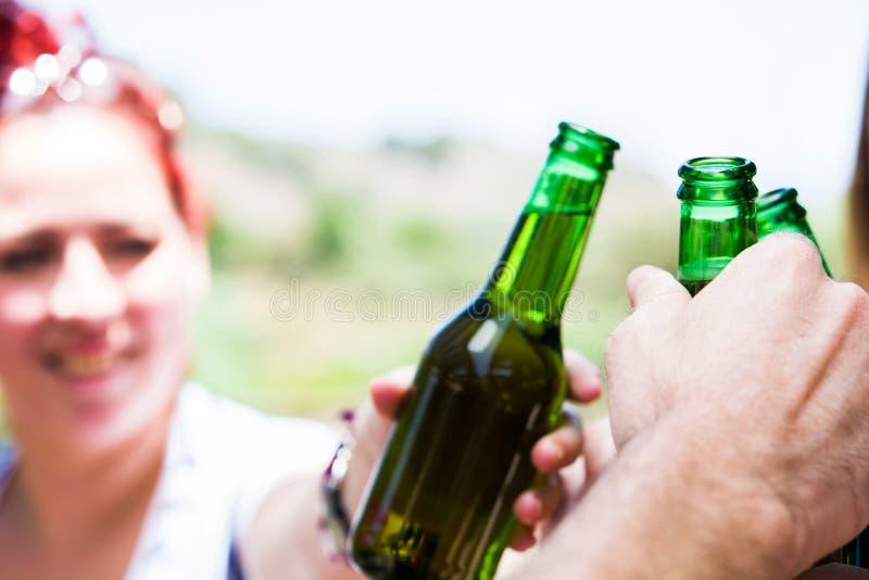 Giorno di picnic con gli amici che incoraggiano con le bottiglie di birra fotografia stock libera da diritti