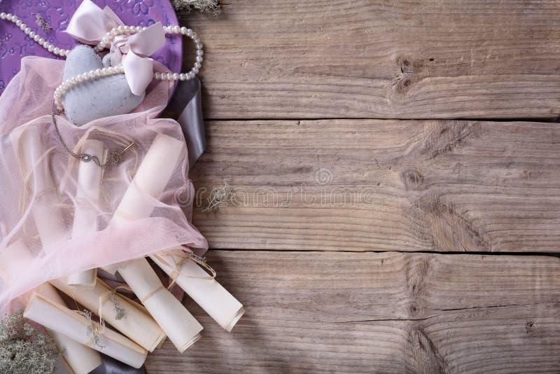 Giorno di Valentine's fissato: cuore, nastro rosa e rotoli d'annata sul fondo rustico del legname galleggiante, spazio della co immagini stock libere da diritti