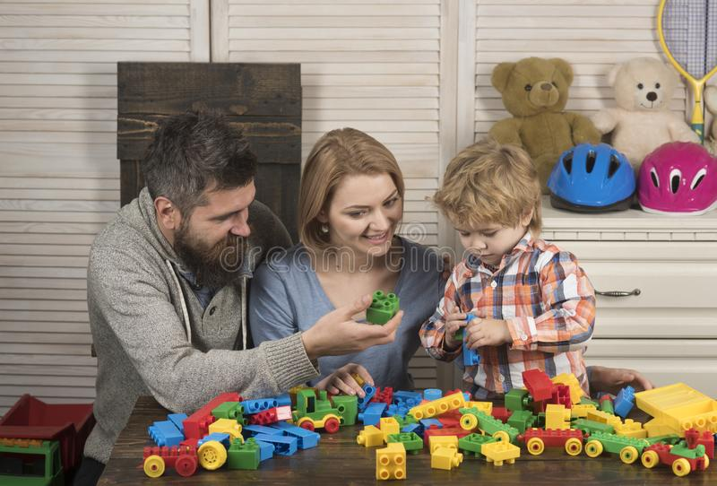 giorno felice dei bambini e della famiglia Ragazzino con il papà e la mamma padre e madre con il costruttore del gioco da bambini fotografia stock libera da diritti