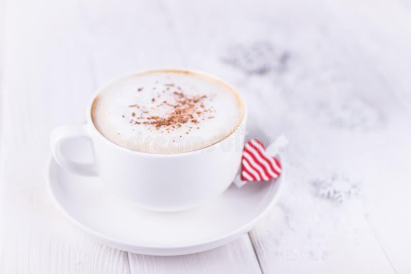 Giorno felice del `s del biglietto di S Tazza bianca con il cuore di rosso e del cappuccino su un fondo di legno bianco Spazio li immagini stock