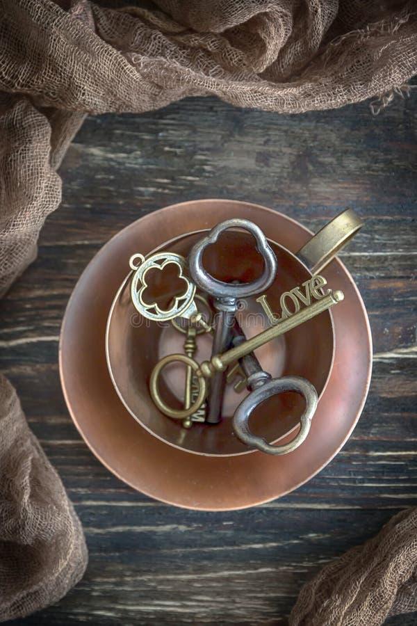 Giorno felice del ` s del biglietto di S. Valentino! La tazza di rame d'annata e la chiave amano sui vecchi precedenti di legno V fotografie stock libere da diritti