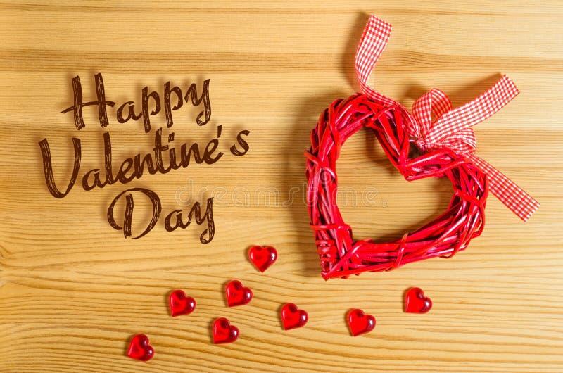 Giorno felice del ` s del biglietto di S. Valentino del segno del cuore su una struttura di legno e piccoli cuori di vetro immagini stock