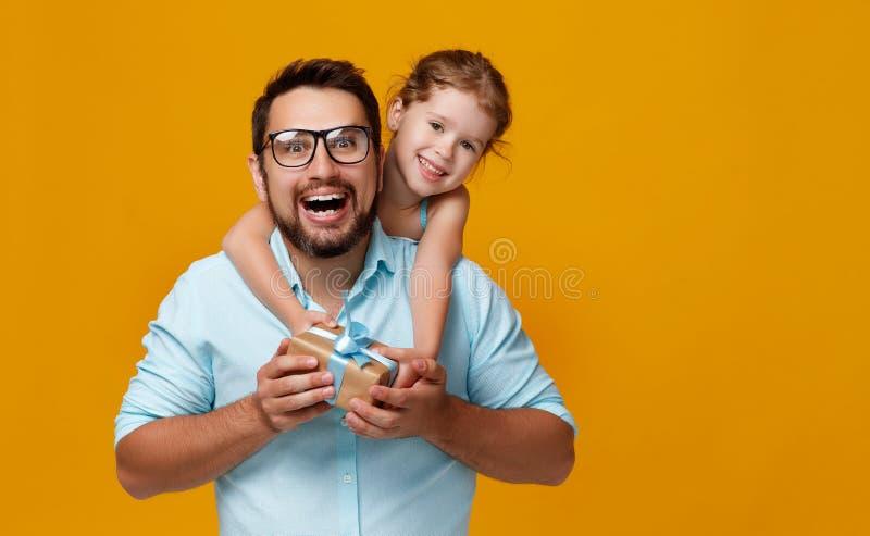 Giorno felice del ` s del padre! papà sveglio e figlia che abbracciano sulla parte posteriore di giallo fotografie stock
