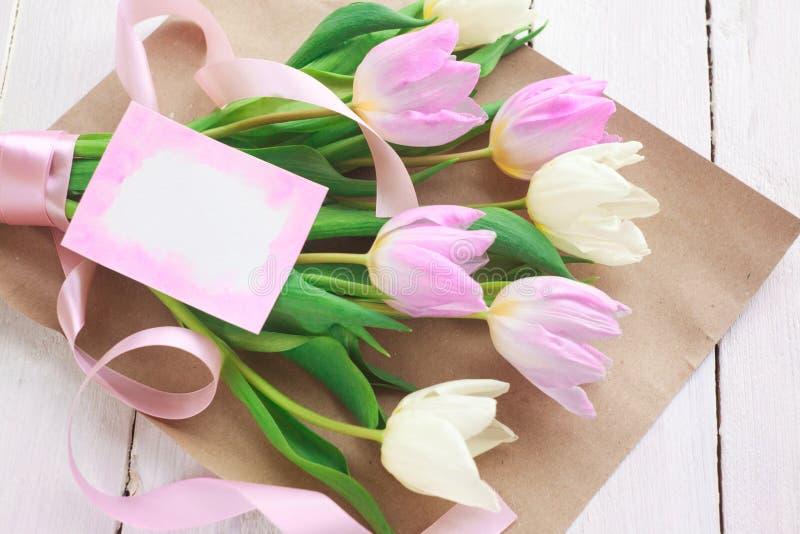 Giorno internazionale del ` s delle donne Un mazzo dei tulipani bianchi e rosa con un nastro su un fondo bianco Cartolina d'augur immagine stock libera da diritti