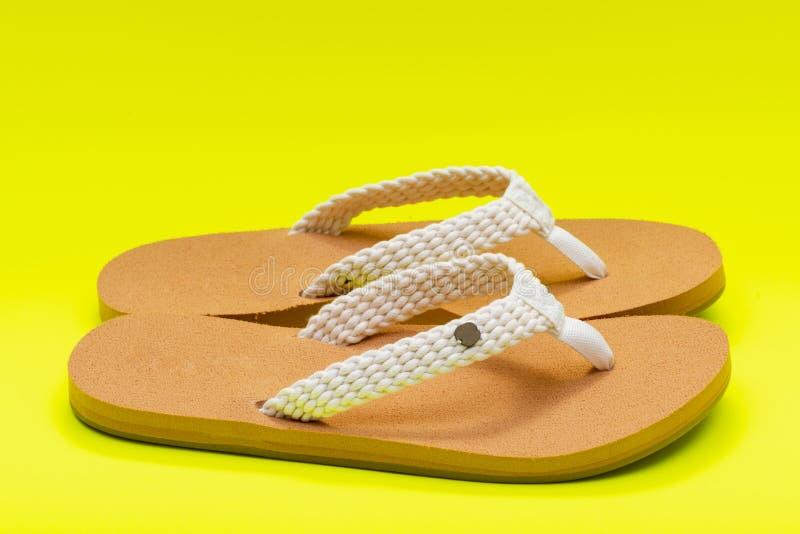 Giorno naturale intrecciato causale Flip Flops della spiaggia del colore delle donne isolato su giallo luminoso fotografia stock