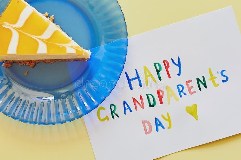 Giorno nazionale felice dei nonni Cartolina d'auguri colorata fatta dai bambini e dal pezzo di dolce sul piatto blu come regalo fotografia stock