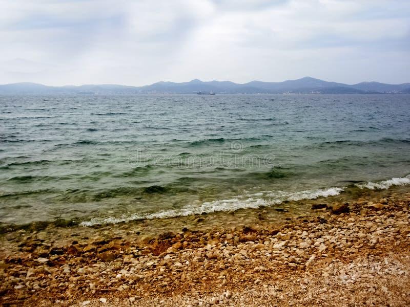 Giorno nuvoloso e Pebble Beach fotografia stock libera da diritti