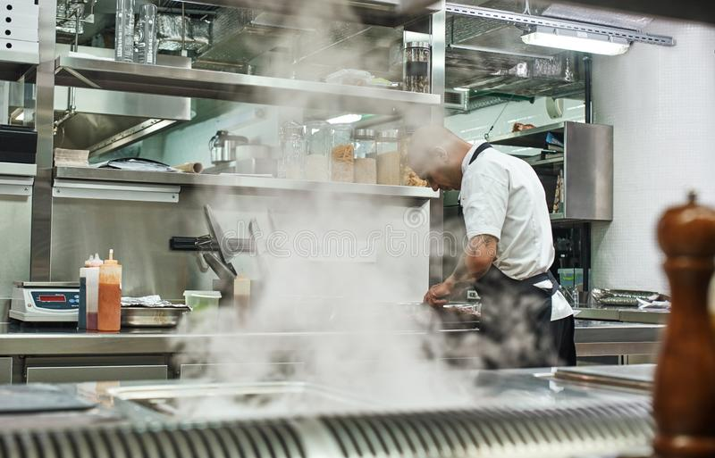 Giorno occupato Punto di vista posteriore del cuoco unico maschio in grembiule che taglia una carne mentre stando in una cucina d fotografie stock libere da diritti