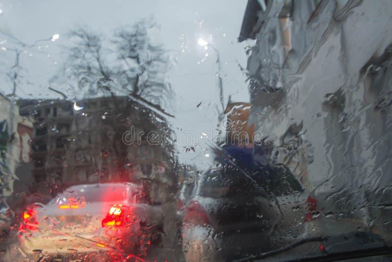 Giorno piovoso nella città, nel traffico e nelle gocce di nad delle automobili di pioggia sul parabrezza dell'automobile fotografia stock libera da diritti