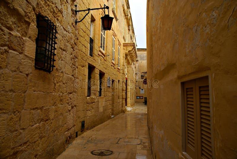 Giorno piovoso sulla vecchia via stretta in Mdina - città silenziosa fotografie stock libere da diritti