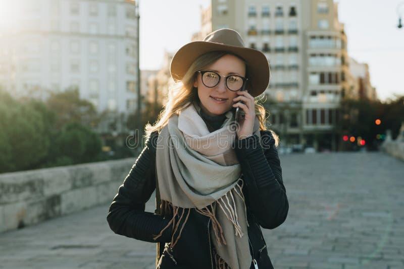 Giorno soleggiato di autunno, lampadina La giovane donna attraente viaggia in cappello e gli occhiali stanno sulla via della citt immagini stock libere da diritti