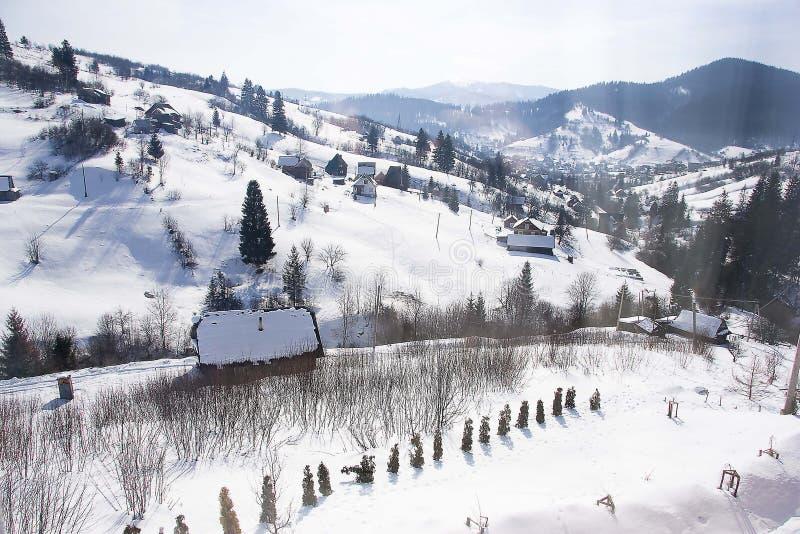 Giorno soleggiato, vista dalla finestra su un paesaggio nevoso di inverno Paesino di montagna, case e recinti fotografie stock libere da diritti