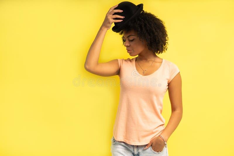Giovane abbigliamento casual d'uso femminile sexy d'avanguardia che posa sopra il fondo giallo immagini stock