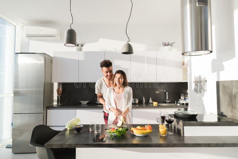 Giovane abbraccio delle coppie in cucina, in uomo ispano e nell'abbraccio asiatico della donna fotografia stock libera da diritti
