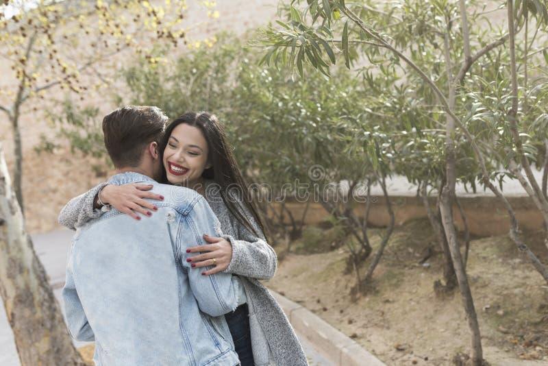 Giovane abbraccio delle coppie in parco all'aperto nel tempo di primavera fotografie stock