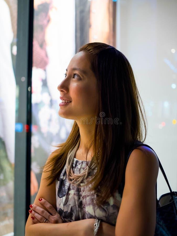Giovane acquisto asiatico attraente, alla moda, alla moda della finestra della donna fotografia stock libera da diritti