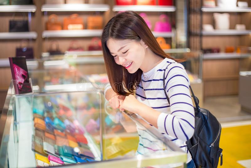 Giovane acquisto asiatico attraente felice della donna ed esaminare merch fotografia stock libera da diritti