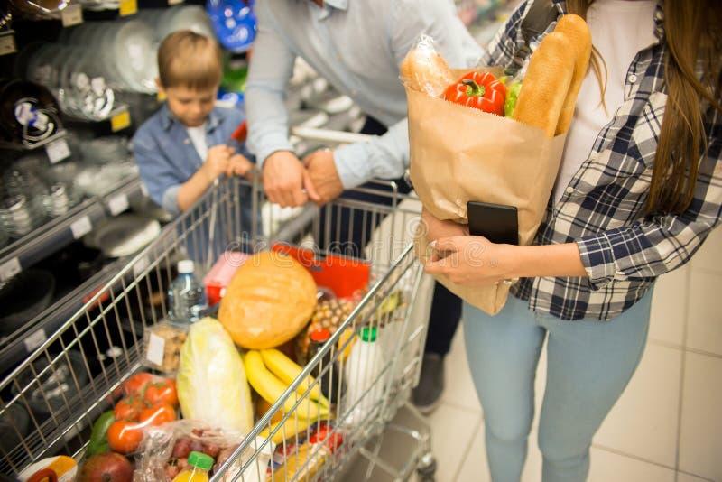 Giovane acquisto felice della famiglia per le drogherie in supermercato fotografia stock libera da diritti