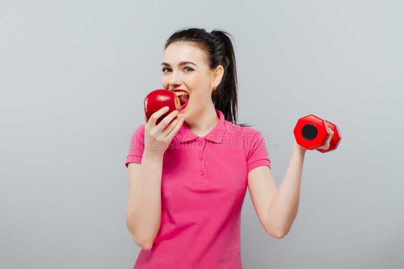 Giovane addestramento asiatico della donna muscolare e mela della mano con le teste di legno rosse, chilogrammo fotografia stock
