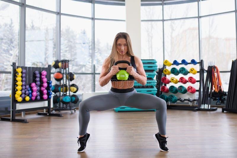 Giovane addestramento atletico della donna con le teste di legno alla palestra Forma fisica e concetto sano di stile di vita Bell immagine stock libera da diritti