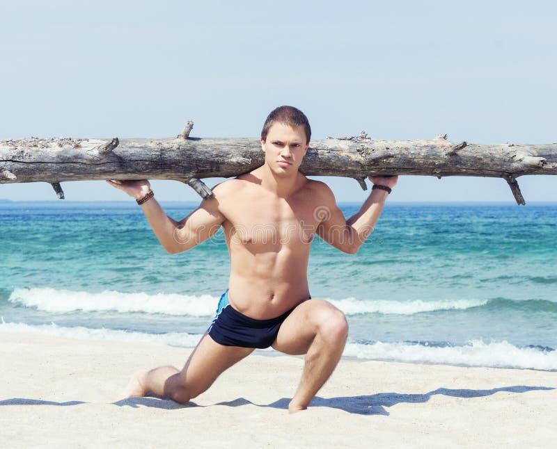 Giovane, addestramento bello ed atletico dell'uomo sulla spiaggia fotografie stock libere da diritti