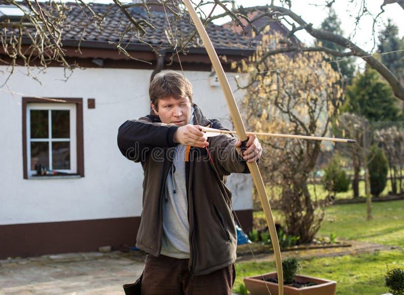 Giovane addestramento dell'arcere con l'arco fotografia stock