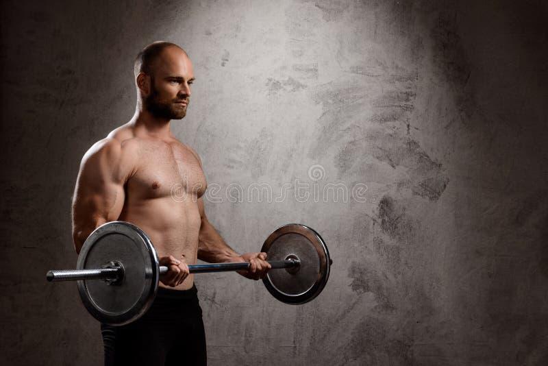 Giovane addestramento potente dello sportivo con il bilanciere sopra fondo scuro fotografia stock