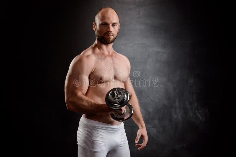 Giovane addestramento potente dello sportivo con le teste di legno sopra fondo nero fotografia stock