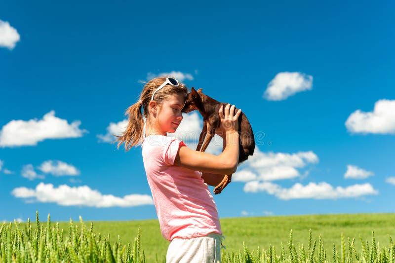 Giovane adolescente allegro nel giacimento di grano con il suo cane favorito fotografia stock libera da diritti